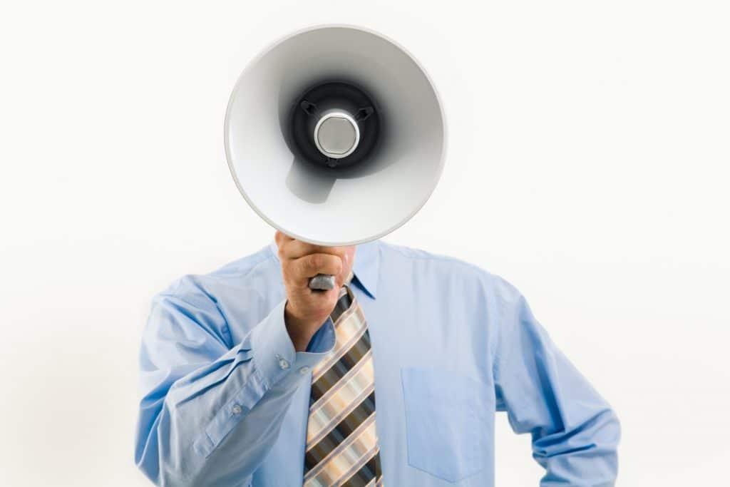 Man communicating with loud speaker to represent Alexa Communication